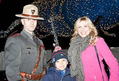 women and son with police officer in front of holiday lights
